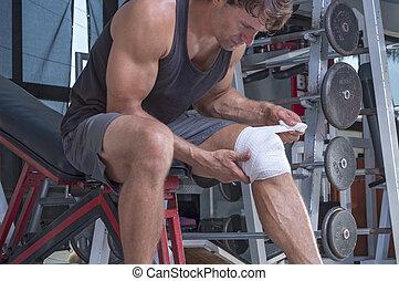 Wrapping knee injury - Muscular Caucasian man wraps knee...