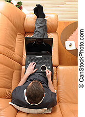 Businessman holding a cup of coffee and working on portable computer on luxurious sofa.