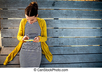 Woman with phone on sunbed - Young woman in yellow sweater...