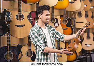 Music store - Man is holding ukelele in music shop.