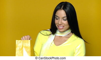 Sexy girl with shopping bag on yellow background