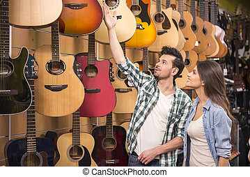 Music store - Man is showing to girl guitar in a music...