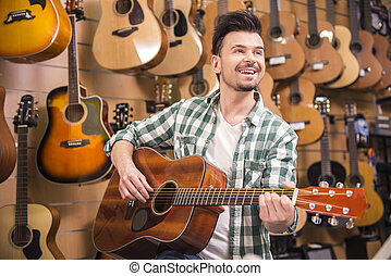 Music store - Man is playing on guitar in music shop