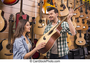 Music store - Man is showing girl guitar in a music store.