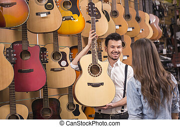 Music store - Man is showing girl guitar in a music store