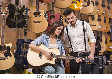 Music store - Young attractive girl is playing guitar near...