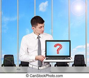 question mark - young businessman holding laptop with...
