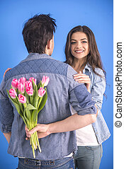 Couple - Guy is holding flower behind him is trying to...