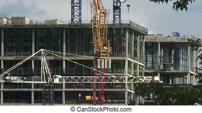 Cranes on construction site working around buildings in...