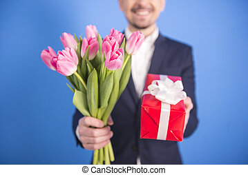 Man with flowers - Close-up handsome young man is giving a...