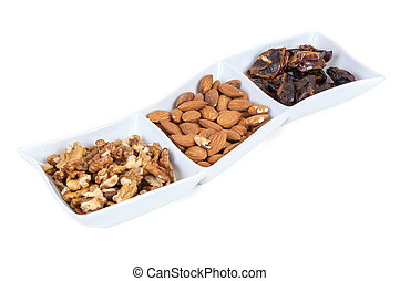 Walnuts almonds and dates in a white dish