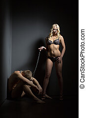 Concept of dominance Woman holds man in chains - Concept of...