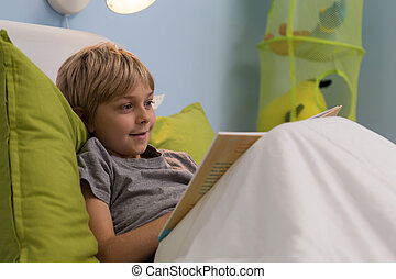 Smiling boy reading book - Smiling ill boy reading book in...
