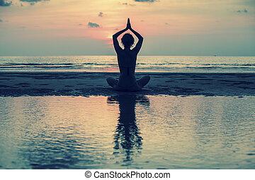 yoga, silueta, joven, mujer, en, el, playa, en, ocaso,...