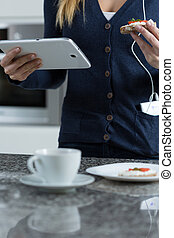 Using tablet during eating sandwich