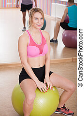 Woman sitting on ball - Young fit woman sitting on fitness...
