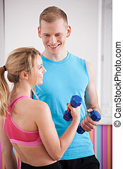 Couple with dumbbells - Two young people exercising with...