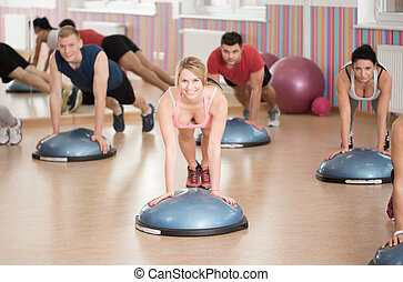 Push-ups on bosu - Fit people doing push-ups on fitness bosu