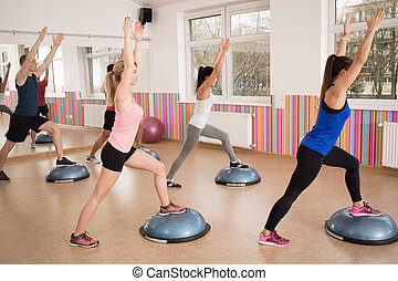 Exercising with bosu - Group of young fit people exercising...