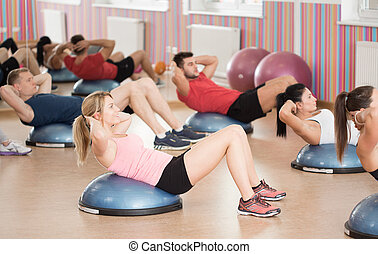 Crunches on bosu - Group of fit people doing crunches on...