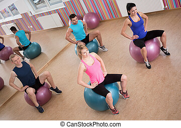 Exercises on ball - Young people doing exercises on fitness...