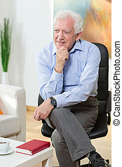 Elderly man sitting on a chair and smiling