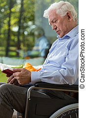Man on wheelchair reading book