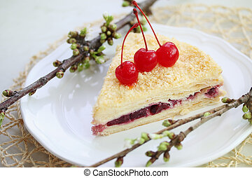 Napoleon cake with cherries on a plate