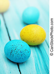 Spotted colored eggs on a wooden board