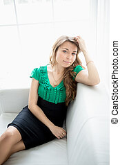 beautiful young woman sitting on white couch next to window