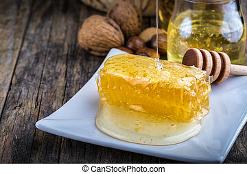 honey dipper and honeycomb, nuts of various kinds - honey...