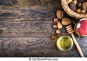 honey dipper and nuts in honey and nuts of various kinds, -...