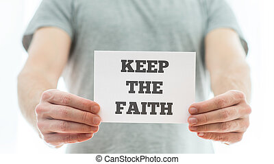 Keep the faith message - Closeup of a homeless man holding...