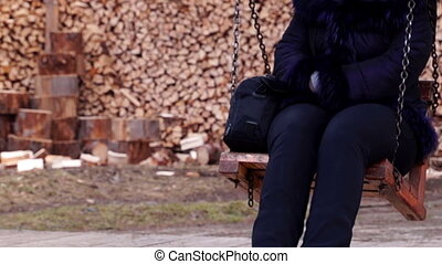 Girl Swinging on a Wooden Swing on a Background of Wood in...