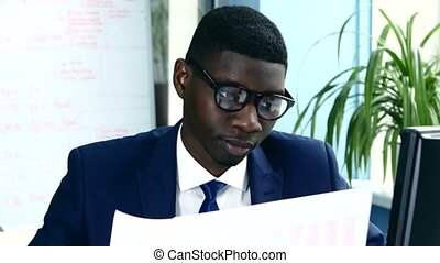 African American with glasses carefully studying business papers sitting at your desk