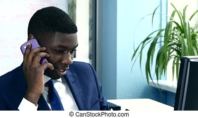 African American businessman on the phone sitting at computer