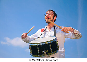 young man in glasses plays on drum