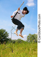 young man jumps with guitar on grass