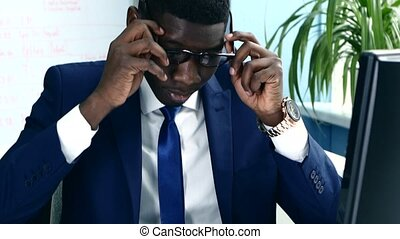 African American with glasses and a business suit carefully studying charts.