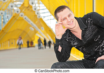 smiling guy sits on yellow footbridge