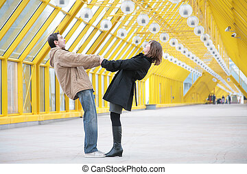 boy and girl hold each other for hands on footbridge