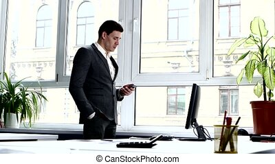 Young man in a nice business suit is phone conversation window