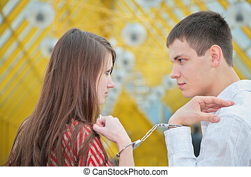 Young couple with handcuffs on footbridge
