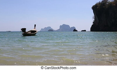 longtail boat drifts against cliffy islands - motor thai...