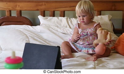 little girl lies in bed among toys and watches cartoons -...