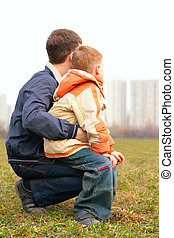son on lap of father outdoor in city from back
