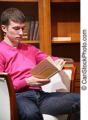 young man reads book in room