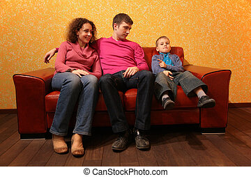Family seating on red leather sofa