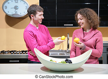 young couple on kitchen with fruits in hands