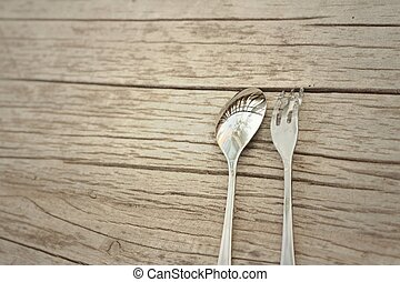 Spoon and fork on a background of brown wood.